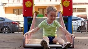 El niño rueda con una diapositiva de los niños almacen de video