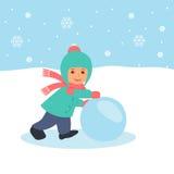 El niño rueda una bola de nieve Paseo al aire libre en vacaciones de invierno Imagen de archivo libre de regalías