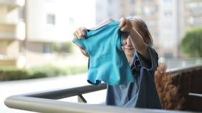 El niño sacude apagado la ropa mojada en el balcón metrajes