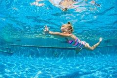 El niño salta bajo el agua en piscina Fotos de archivo