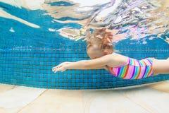 El niño salta bajo el agua en piscina Imágenes de archivo libres de regalías
