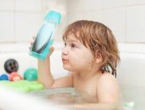 El niño se baña con la botella del champú Imagen de archivo libre de regalías