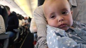 El niño se cae dormido en el avión en las manos del ` s de la mamá metrajes