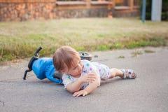 El niño se cayó abajo de su bici Foto de archivo