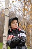 El niño se coloca sobre un árbol en parque del otoño Fotos de archivo