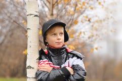 El niño se coloca sobre un árbol en parque del otoño Foto de archivo