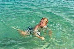 El niño se divierte en el océano Imagenes de archivo