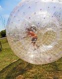 El niño se divierte en la bola de Zorbing Fotos de archivo libres de regalías