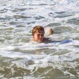 El niño se divierte en las ondas Fotografía de archivo