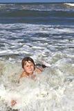 El niño se divierte en las ondas Fotos de archivo