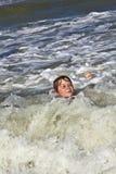 El niño se divierte en las ondas Foto de archivo