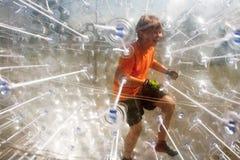 El niño se divierte mucho en la bola de Zorbing Fotos de archivo