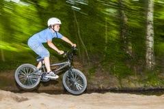 El niño se divierte que salta con la bici Imagen de archivo