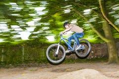 El niño se divierte que salta con la bici del thé sobre una rampa Fotos de archivo