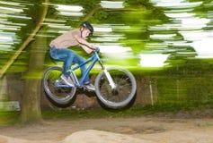El niño se divierte que salta con la bici sobre una rampa Foto de archivo