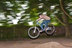 El niño se divierte que salta con la bici sobre una rampa Fotos de archivo libres de regalías