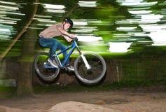 El niño se divierte que salta con la bici sobre una rampa Fotos de archivo