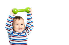 El niño se está sentando con pesas de gimnasia a disposición Imagen de archivo