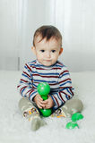 El niño se está sentando con pesas de gimnasia a disposición Foto de archivo libre de regalías