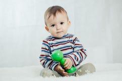 El niño se está sentando con pesas de gimnasia a disposición Imagen de archivo libre de regalías