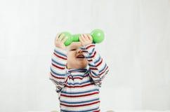 El niño se está sentando con pesas de gimnasia a disposición Fotografía de archivo