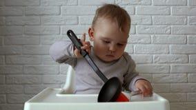 El niño se está sentando detrás de la tabla de los niños y examina el cepillo y la cucharón del silicón metrajes