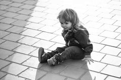 El niño se está sentando en el asfalto El niño pequeño se sienta en el pavimento fotografía de archivo libre de regalías