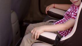 El niño se está sentando en asiento de carro en coche, él lleva a cabo sus manos en los brazos de la silla almacen de video
