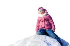 El niño se está sentando en una montaña de la nieve y de la sonrisa Imagen de archivo libre de regalías