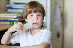 El niño se sienta con la cinta sellada boca Fotografía de archivo libre de regalías