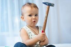 El niño se sienta con un martillo Fotografía de archivo