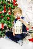 El niño se sienta en el árbol de navidad y juega el hom de la Navidad Fotos de archivo
