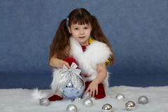 El niño se sienta en azul con la bola del árbol de navidad Fotos de archivo