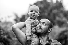 El niño se sienta en el hombro y la sonrisa del papá foto de archivo