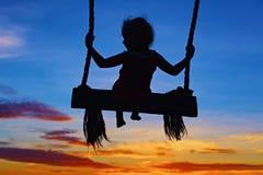 El niño se sienta en el oscilación en fondo colorido del cielo de la puesta del sol Fotografía de archivo libre de regalías