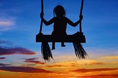 El niño se sienta en el oscilación en fondo colorido del cielo de la puesta del sol Fotos de archivo libres de regalías