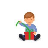 El niño se sienta en el piso y abre una caja con un regalo Imagen de archivo libre de regalías