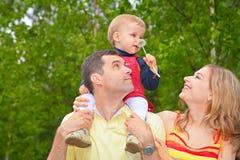 El niño se sienta en hombros del padre con el diente de león imagen de archivo libre de regalías