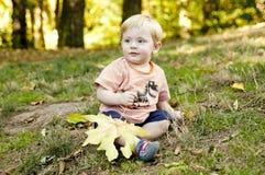 El niño se sienta en la hierba en el parque Imagen de archivo libre de regalías