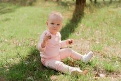 El niño se sienta en la hierba y los controles dos conos que miran la c imagen de archivo