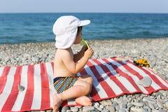 El niño se sienta en la playa de piedra y mira en el mar Fotos de archivo libres de regalías