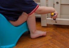 El niño se sienta en el pote y repara su cama Fotos de archivo libres de regalías