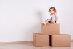 El niño se sienta en un cuarto en las cajas Imagen de archivo libre de regalías