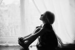 El niño se sienta en un travesaño de la ventana Fotografía de archivo