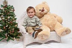 El niño se sienta por el oso y el árbol de navidad de peluche Fotografía de archivo