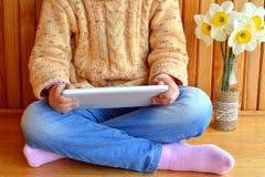 El niño se sienta sosteniendo una tableta en manos Florero de narcisos Fondo de madera Foto de archivo libre de regalías