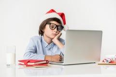 El niño serio está trabajando en el cuaderno Imagen de archivo libre de regalías