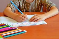 El niño sienta y dibuja las flores Foto de archivo