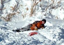 El niño Sledding cae en el banco de la nieve Fotos de archivo