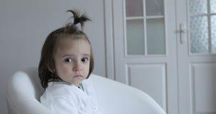 el niño soñoliento de 4K A está haciendo girar en una silla blanca almacen de metraje de vídeo